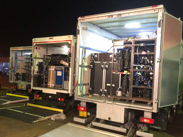Nighttime photograph of fully loaded trucks with back door open